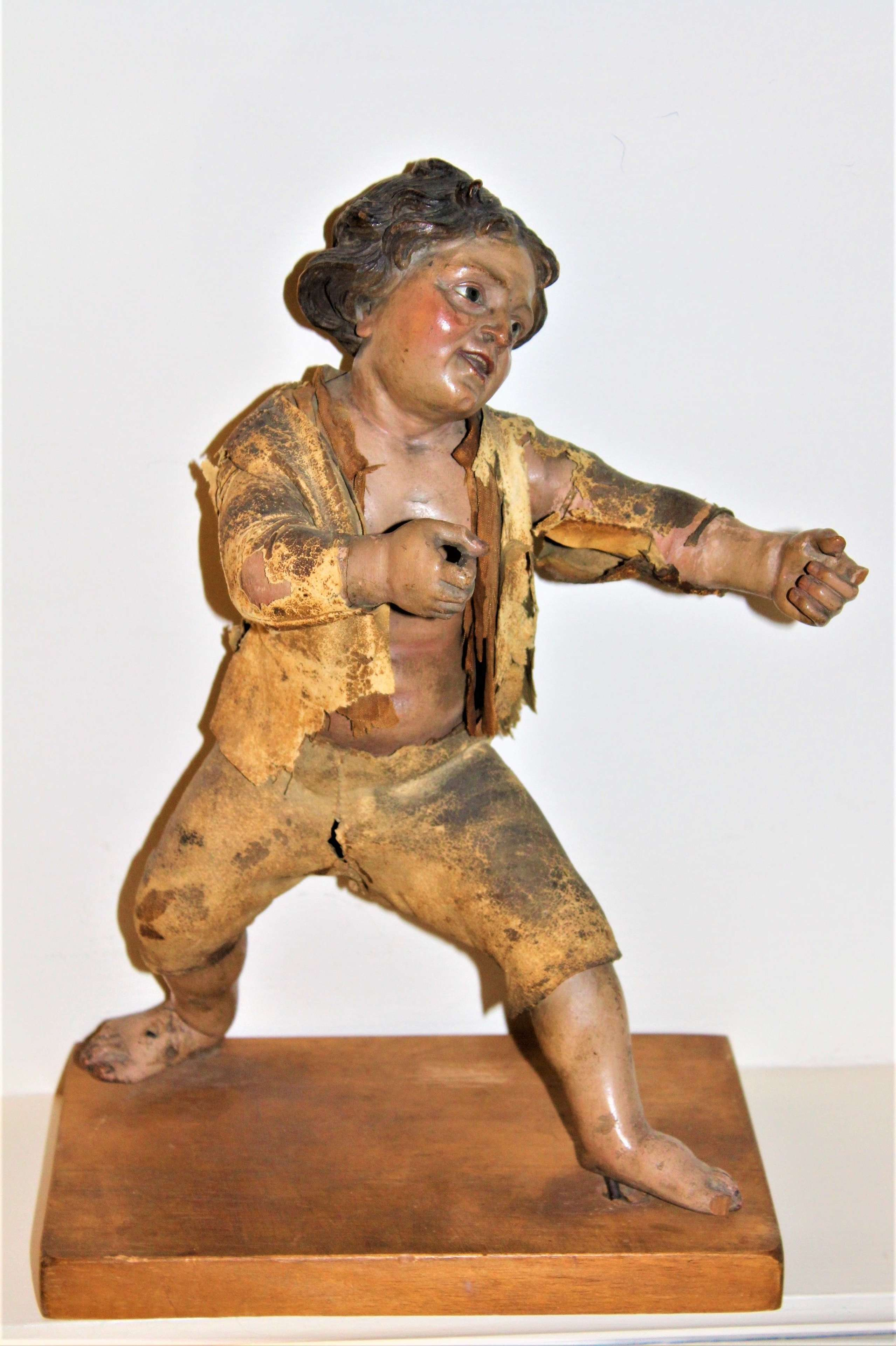 A polychromed carved wood figure of a street urchin