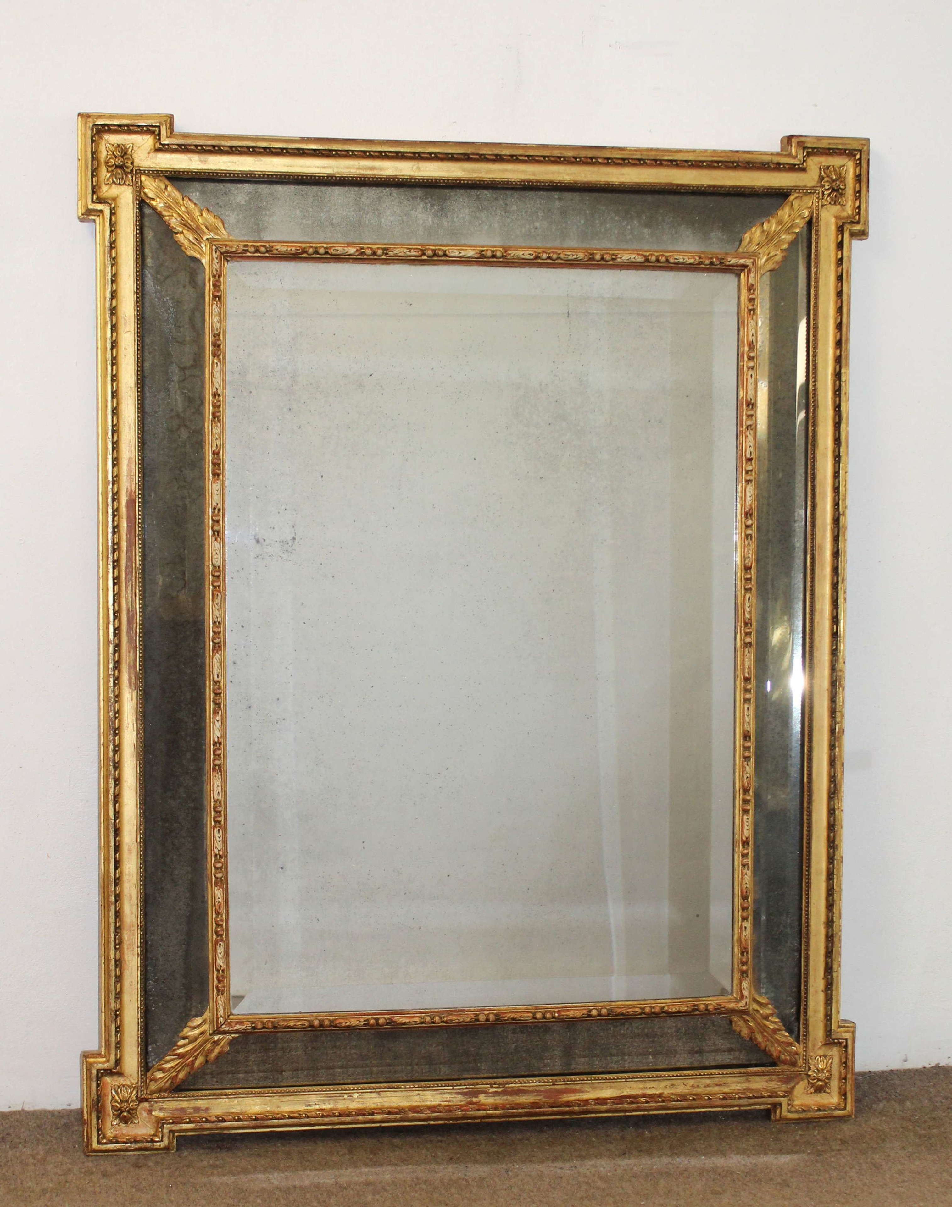 Antique French gilt cushioned mirror with foxed mercury glass