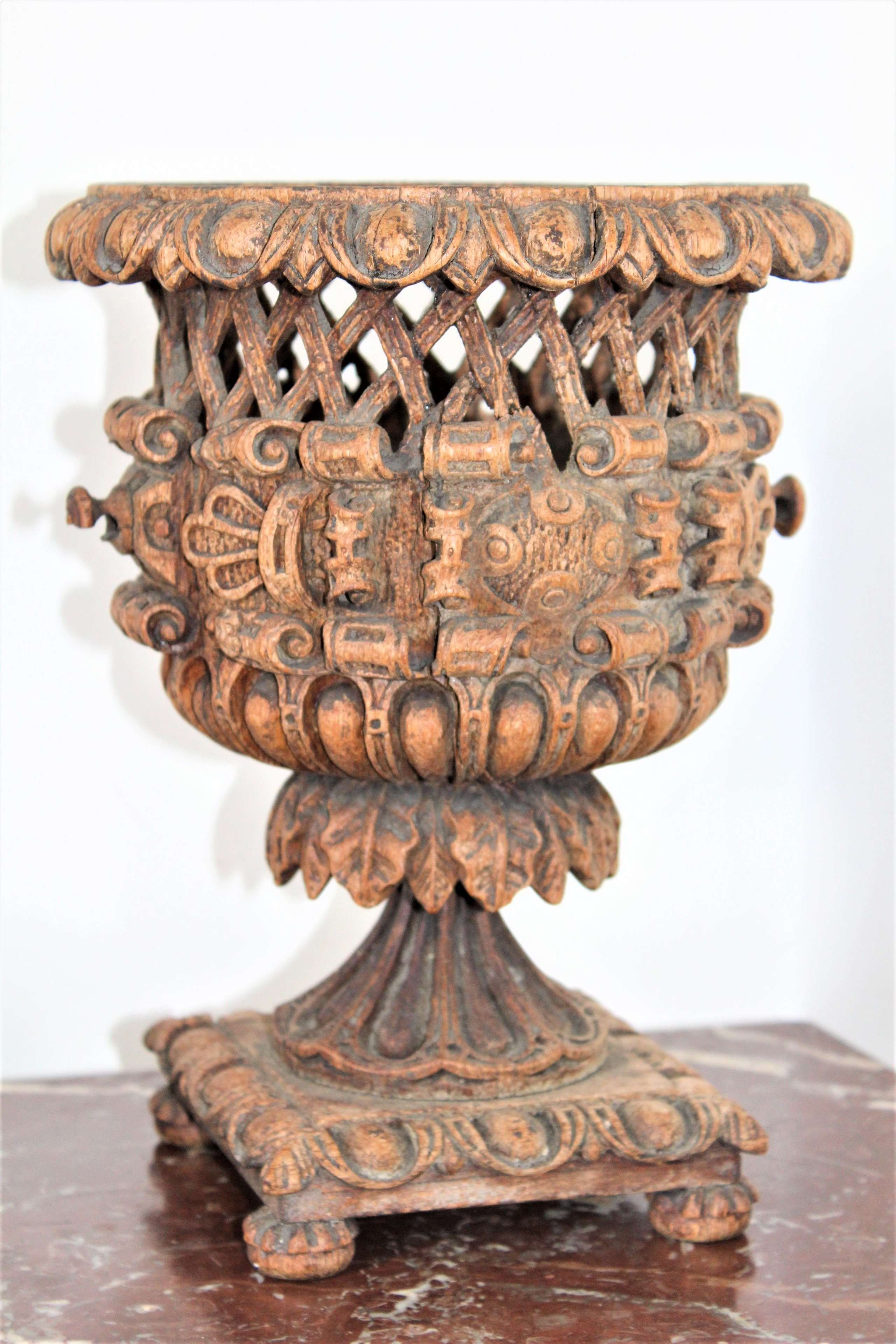 A carved wood jardiniere with pierced diaper and excentric relief side