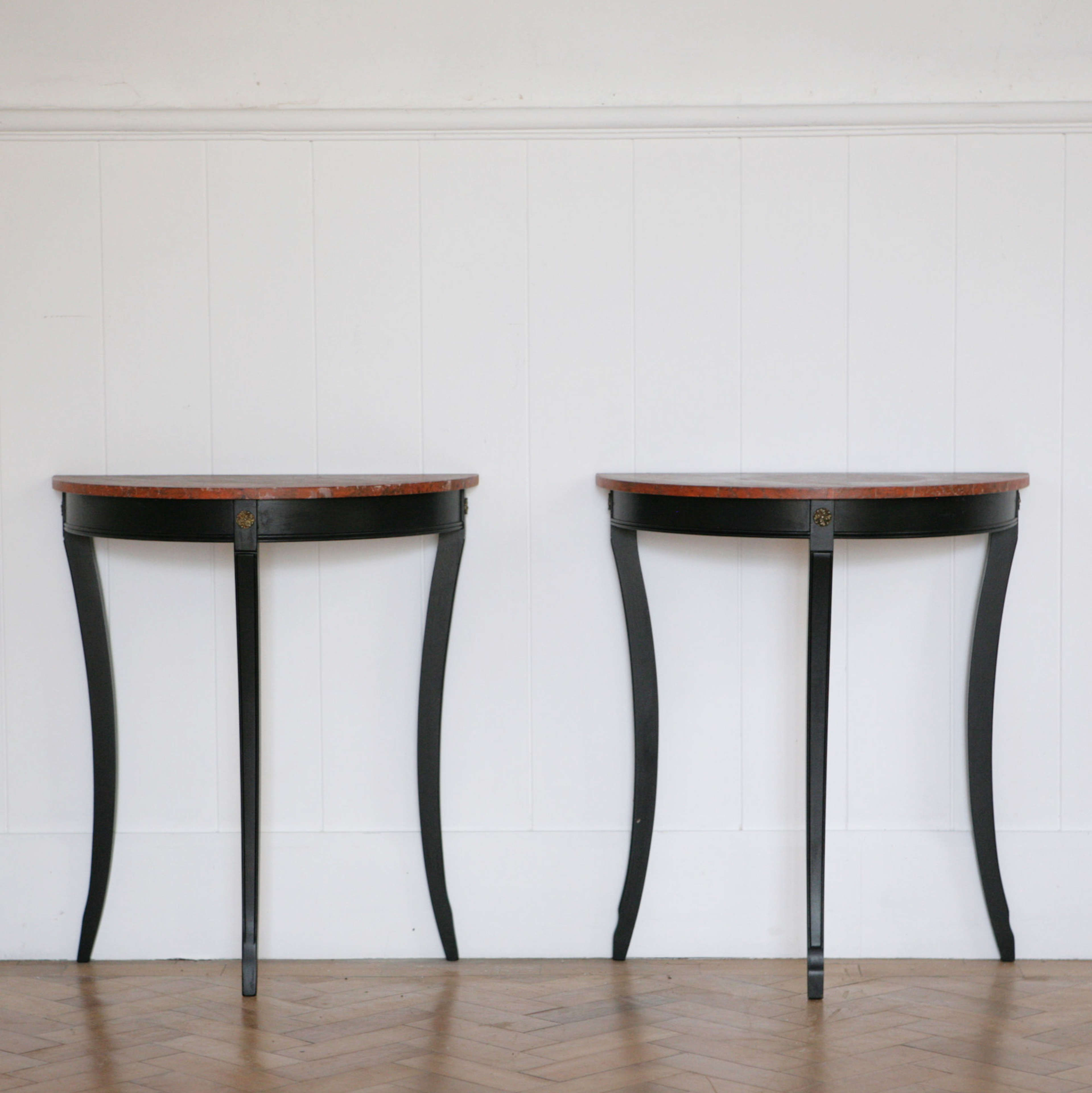 Pair of ebonised console tables with faux marble tops.