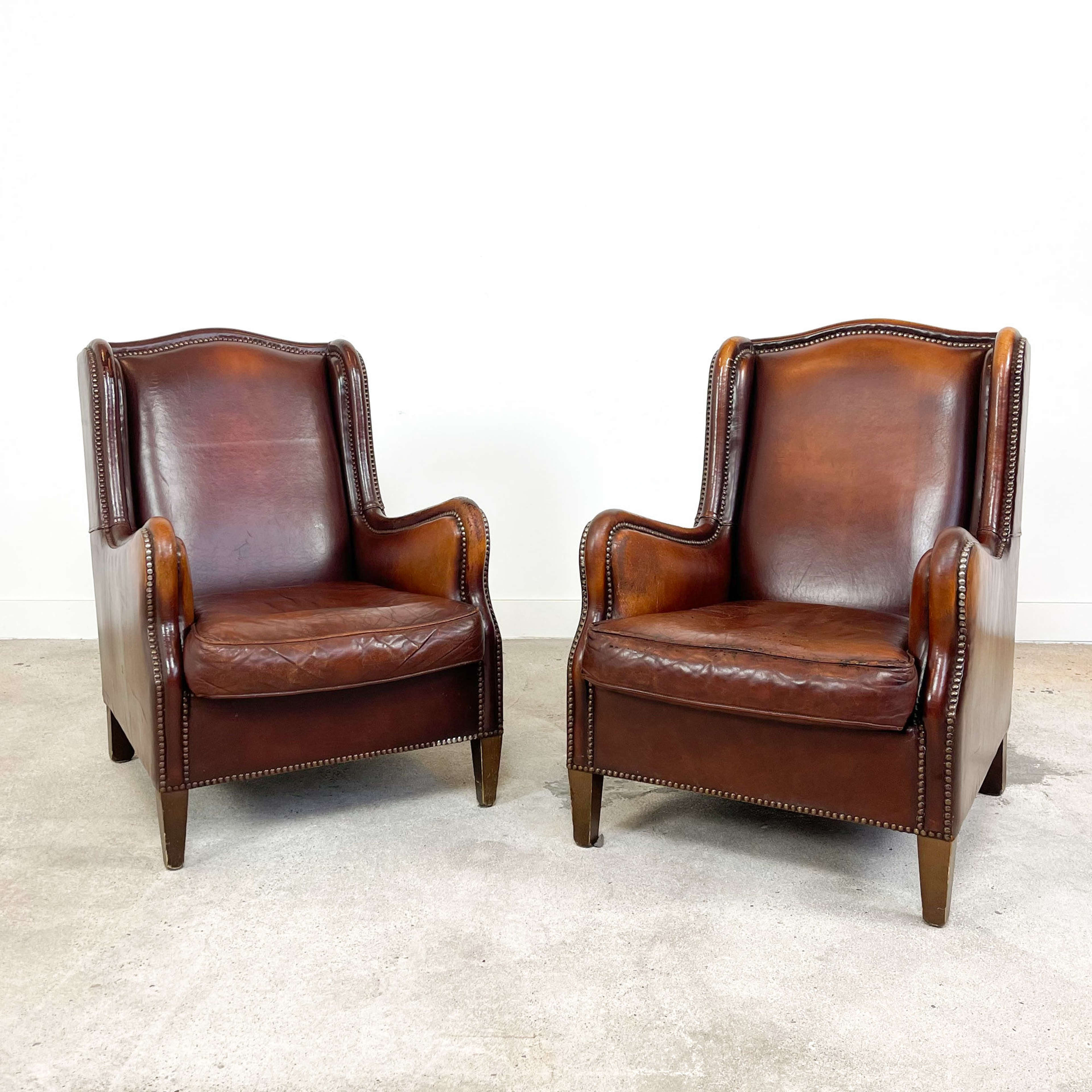 Set of two vintage sheep leather wingback armchairs