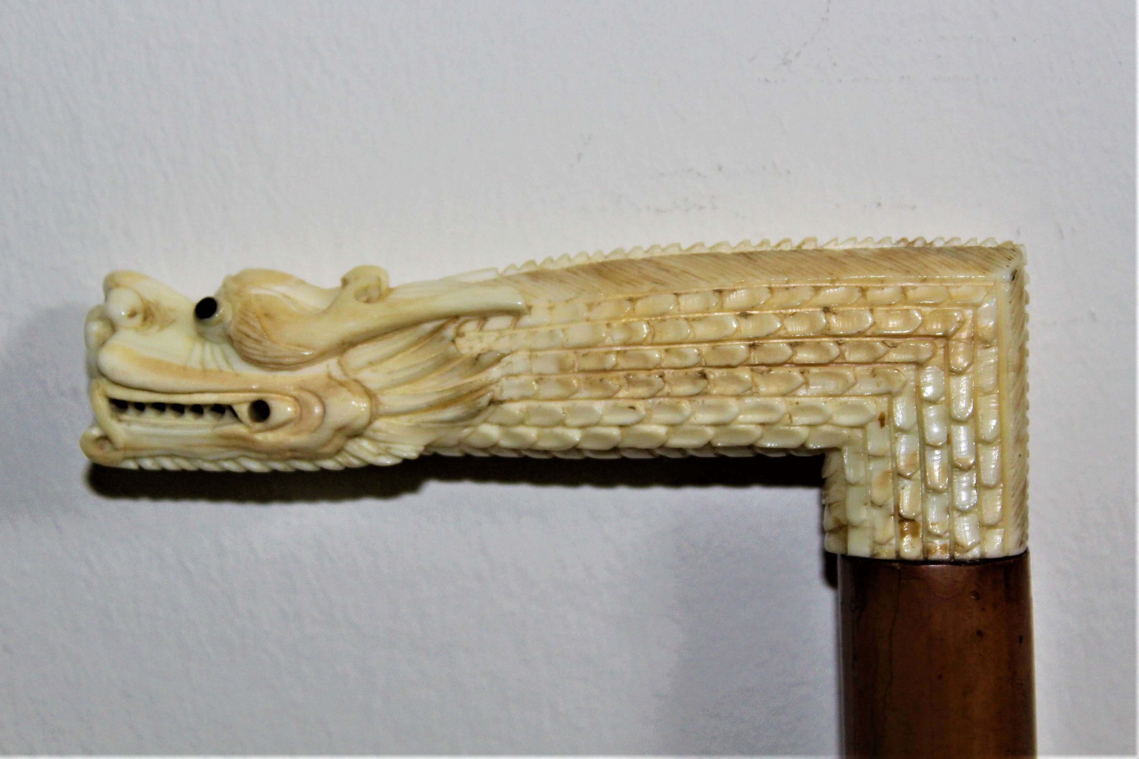 A very fine walking stick with an intricately carved top of a dragon