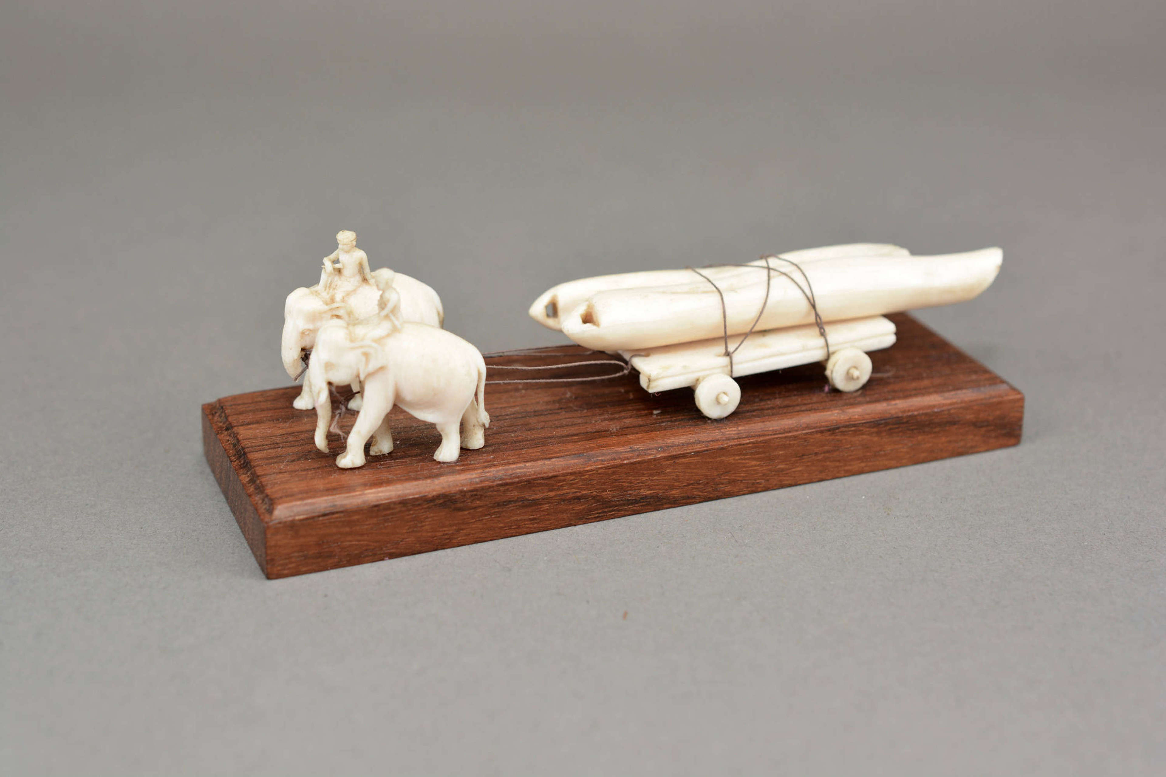 Hand carved model elephants pulling a log cart