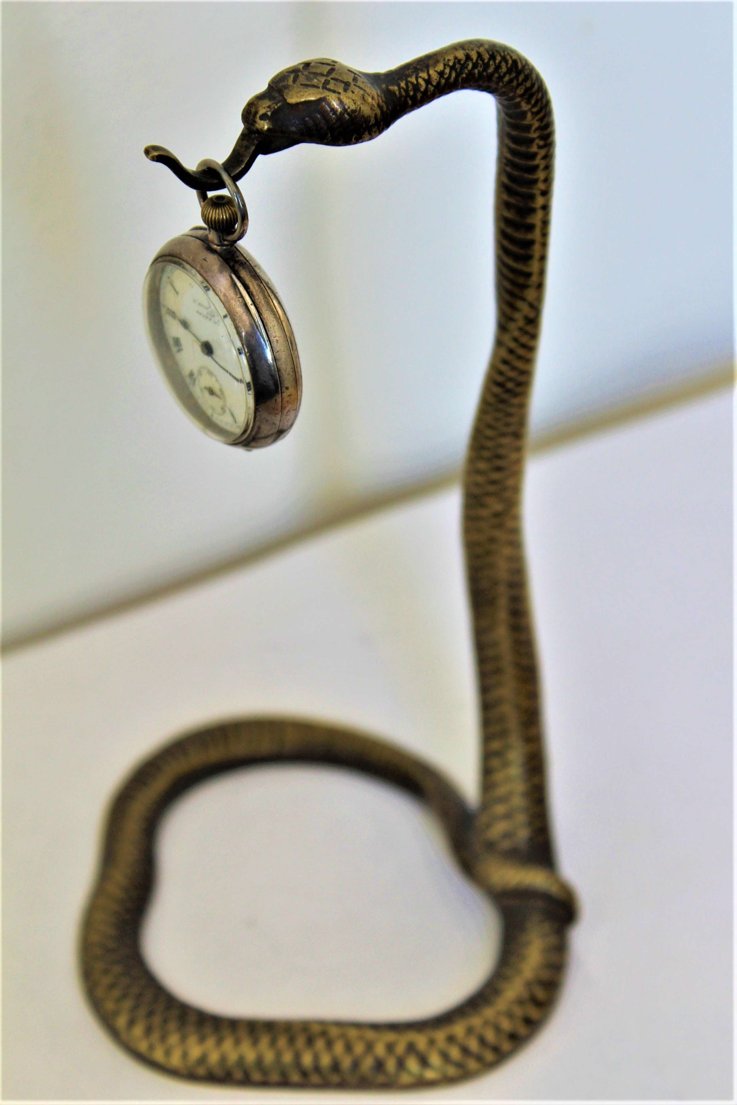 A tall and very stylish bronze / brass watch stand watch not included