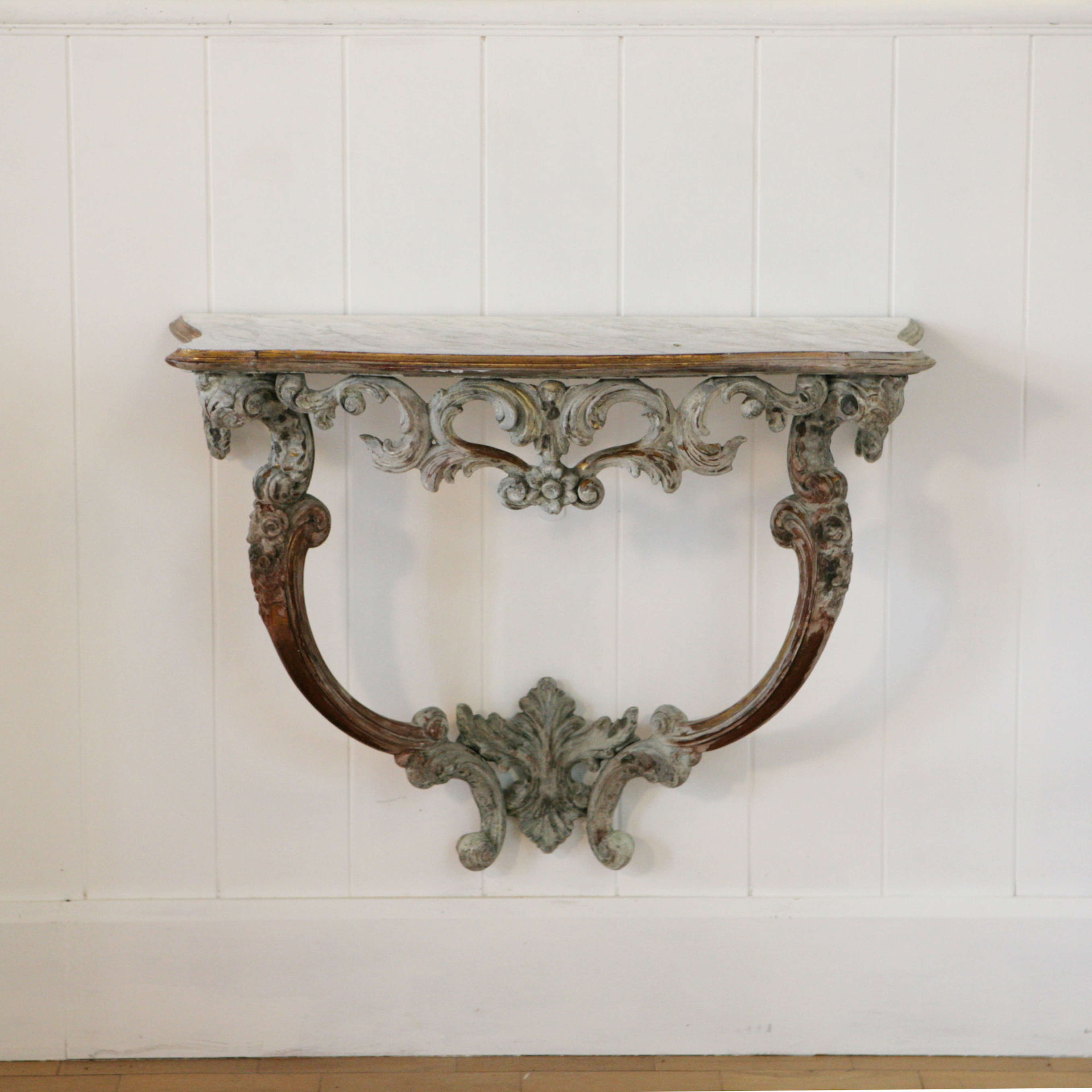 Carved, gilt and gesso console table with faux marble top.